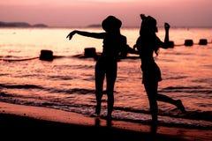 Silhouette de la femme deux ayant l'amusement sur la plage de mer Photos libres de droits