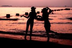 Silhouette de la femme deux ayant l'amusement sur la plage de mer Photo stock
