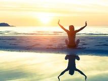 Silhouette de la femme s'asseyant sur la plage pendant le coucher du soleil étonnant, avec la réflexion dans l'eau Photographie stock libre de droits
