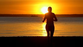 Silhouette de la femme sportive de coureur courant sur la plage d'océan de mer au coucher du soleil Taqueur femelle pulsant en na banque de vidéos