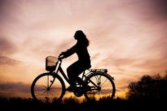 Silhouette de la fille sur la bicyclette photo stock