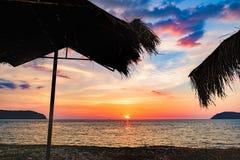Silhouette de la hutte de plage et du coucher de soleil Image libre de droits