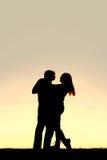 Silhouette de la jeune danse heureuse de couples au coucher du soleil Image stock
