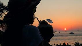 Silhouette de la jeune fille de hippie de métis buvant l'eau thaïlandaise fraîche Coctail de noix de coco sur la plage contre bea banque de vidéos