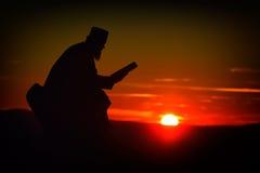 Silhouette de la lecture de prêtre dans la lumière de coucher du soleil Photographie stock
