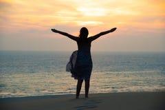 Silhouette de la liberté et de la fille heureuse sur la plage images stock