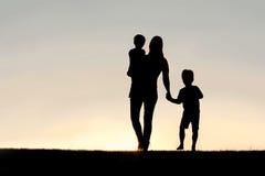 Silhouette de la mère de marche et des enfants en bas âge tenant des mains à Images stock