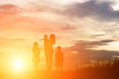 silhouette de la mère, du bébé, de la fille et du fils fa de attente debout Photos libres de droits
