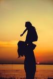 Silhouette de la mère et de l'enfant appréciant la vue à la rive Photo stock