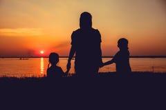 Silhouette de la mère et de l'enfant appréciant la vue à la rive Photos stock