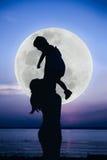 Silhouette de la mère et de l'enfant appréciant la vue à la rive Photos libres de droits