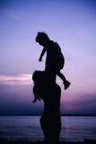 Silhouette de la mère et de l'enfant appréciant la vue à la rive Images stock