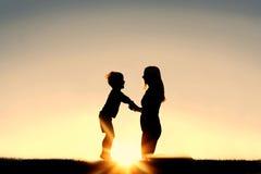 Silhouette de la mère et de l'enfant en bas âge tenant des mains au coucher du soleil Image stock