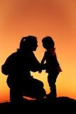 Silhouette de la mère et de la fille étreignant la main ensemble aux soleils Image libre de droits