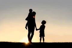 Silhouette de la mère et des enfants en bas âge tenant des mains au coucher du soleil Image stock