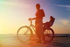 Silhouette de la mère et du bébé faisant du vélo au coucher du soleil Photographie stock libre de droits