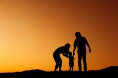 Silhouette de la mère et du fils de père jouant dehors au coucher du soleil Photos stock