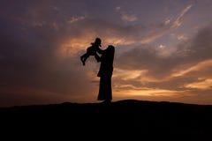 Silhouette de la mère qui tourne l'enfant contre un coucher du soleil Images stock