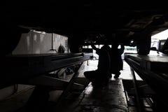 Silhouette de la mécanique réparant la voiture au garage de petit atelier Photographie stock libre de droits