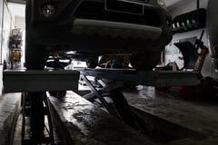 Silhouette de la mécanique réparant la voiture au garage de petit atelier Photographie stock