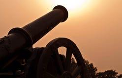 Silhouette de la mise à feu de canon de bataille vers le Sun images libres de droits