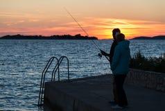 Silhouette de la pêche adulte de couples au coucher du soleil Photo stock