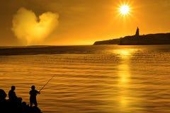 Silhouette de la pêche affectueuse de père et de fils Photographie stock