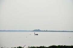 Silhouette de la pêche de pêcheur sur le bateau en bois en Nong Han l Image libre de droits