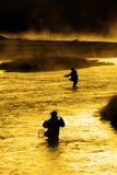 Silhouette de la pêche Flyfishing de l'homme à la lumière du soleil d'or de rivière Images stock