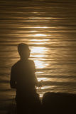 Silhouette de la personne attrapant le soleil dans le son Photos stock
