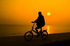 Silhouette de la personne qui monte une bicyclette près de l'eau de mer avec le s Images libres de droits