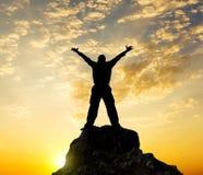 Silhouette de la personne se tenant sur une roche dans les faisceaux d'un declin Photo stock