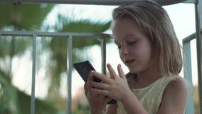 Silhouette de la petite fille à l'aide du smartphone banque de vidéos