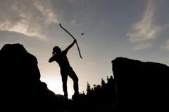 silhouette de lancement d'homme de flèche Photographie stock libre de droits