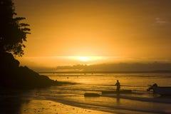 Silhouette de lever de soleil avec des bateliers Images stock