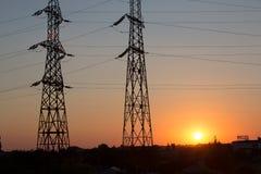 Silhouette de ligne électrique de transmission sur le coucher du soleil Image libre de droits