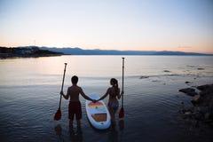 Silhouette de mâle, femelle avec le ressac de petite gorgée et la palette à l'océan Mode de vie de concept, sport, amour Image libre de droits