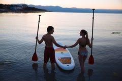 Silhouette de mâle, femelle avec le ressac de petite gorgée et la palette à l'océan Mode de vie de concept, sport, amour Photos libres de droits