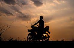 Silhouette de mâle tout en conduisant à la maison par le travail le soir Photos stock