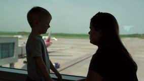 Silhouette de mère avec sa position de fils à la fenêtre dans l'aéroport banque de vidéos