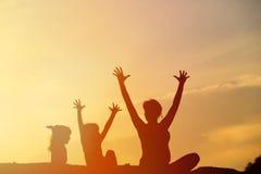 Silhouette de mère et d'enfants heureux au coucher du soleil Photo libre de droits