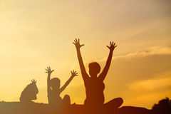 Silhouette de mère et d'enfants heureux au coucher du soleil Images libres de droits