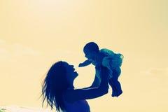 Silhouette de mère et de bébé au coucher du soleil Photo libre de droits
