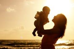 Silhouette de mère et de bébé au coucher du soleil Images stock