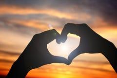 Silhouette de main dans la forme de coeur au fond de coucher du soleil de ciel Image stock