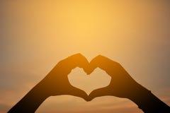 Silhouette de main dans la forme de coeur au backgrou de coucher du soleil de ciel Image libre de droits