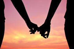 Silhouette de main dans la forme de coeur au backgrou de coucher du soleil de ciel Photos stock