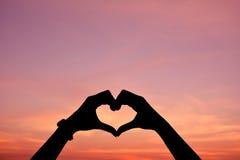 Silhouette de main dans la forme de coeur au backgrou de coucher du soleil de ciel Photo stock