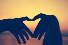 Silhouette de main de forme d'amour sur le fond de ciel Photographie stock