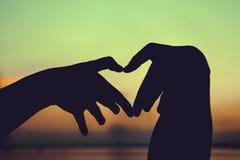 Silhouette de main de forme d'amour sur le fond de ciel Type de cru Images stock